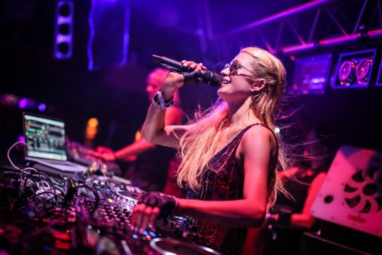 amnesia nightclub ibiza celebrity paris hilton being a dj playing music and singing in the microphone pretty blonde girl having fun making music