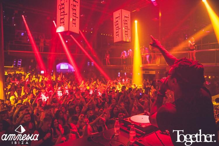 Amnesia nightclub Ibiza dj singing for full crowd red and yellow lights