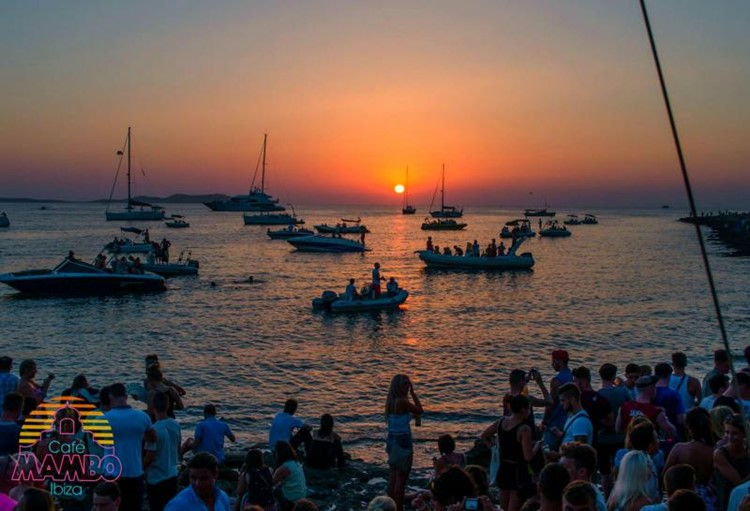 Café Mambo club Ibiza view of crowd on the beach looking at boats and sunset