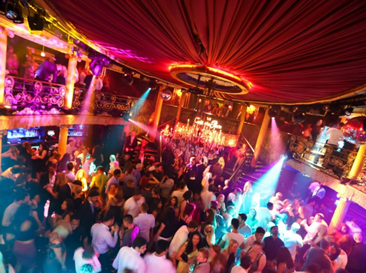 cafe de paris nightclub london twisted circus having a magical amazing show people being happy clapping and dancing colored lights and view of the red ceiling