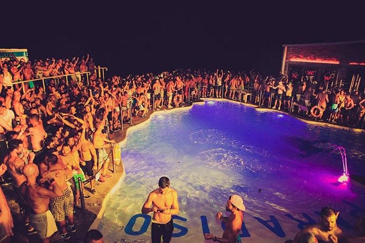 Cavo Paradiso nightclub Mykonos full crowd partying next to the centered swiming pool people in bikinies having fun
