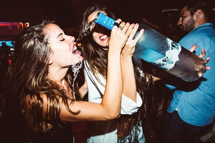 Cavo Paradiso nightclub Mykonos one girl pouring big bottle of alcohol vodka on another's girl face and mouth pretty girls having fun
