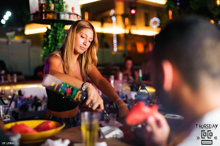 Coco nightclub Tel Aviv pretty blonde waitress pouring drinks at bar