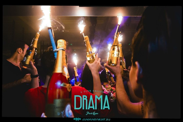 Drama nightclub london champagne and alcohol bottles being served at a vip private table party people having fun and drinking