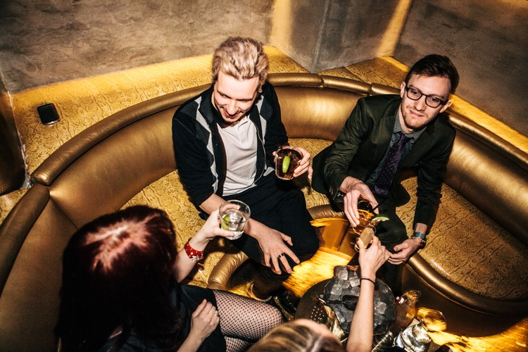 gilded lily nightclub new york handsome men dressed in suits formal dress code drinking alcohol sitting on gold couch