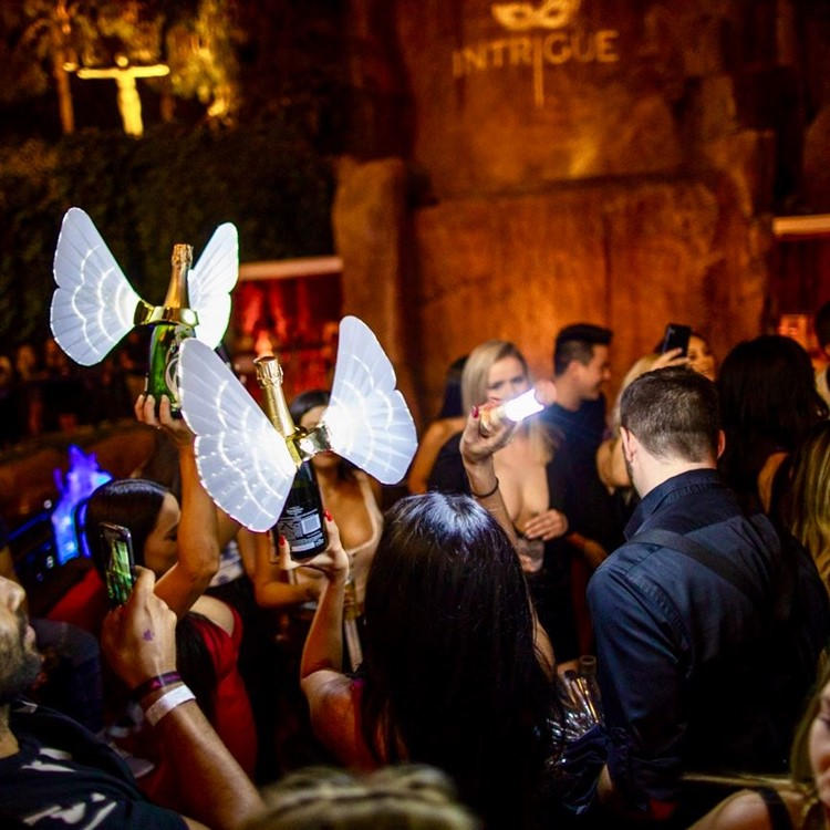 intrigue nightclub las vegas big party event alcoholic drinks champagne being served with white butterfly wings attached to the bottles