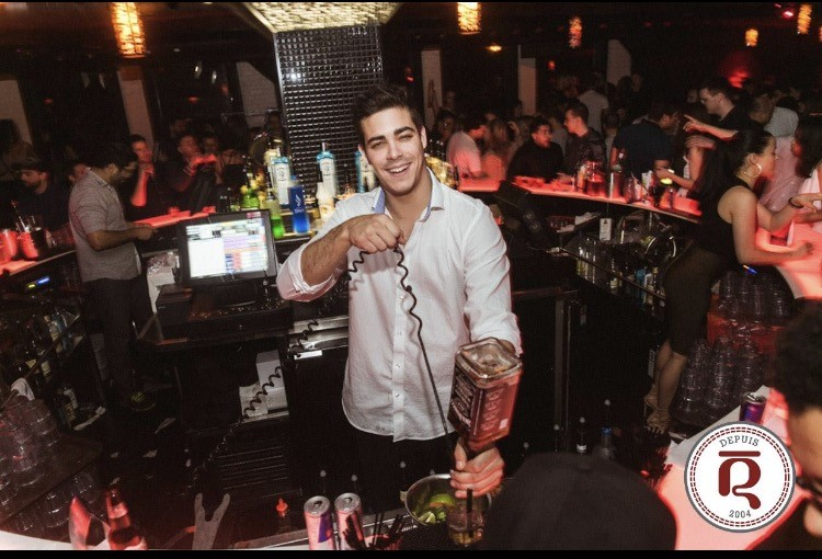 Le Rouge nightclub Montreal barman pouring alcohol drinks at bar