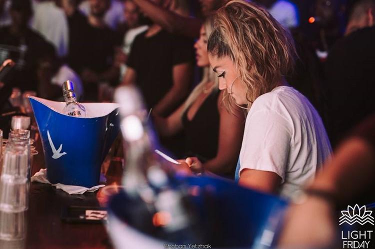 Light House nightclub Tel Aviv blonde girl next to champagne bottle holders drinking