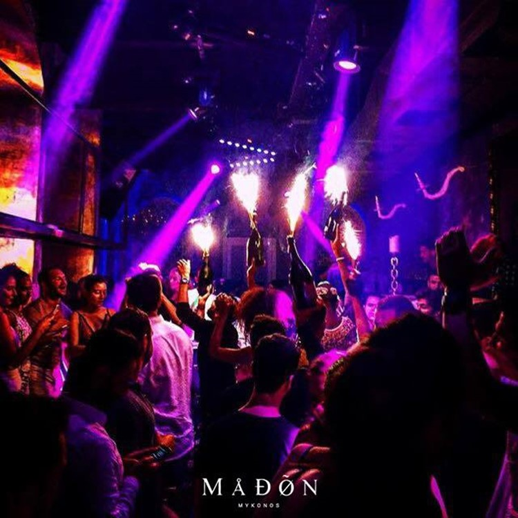 Madon nightclub Mykonos bottles of champaigne bringed to celebrating table