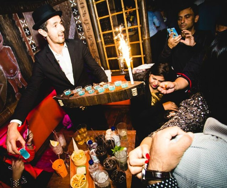 mahiki kensington nightclub london waiter serving alcohol drinks shots to a table booking group of women and men celebrating and having fun