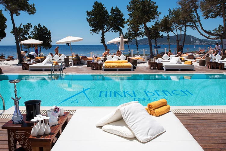 Nikki Beach beachclub Ibiza view of the swimming pool and lounge area palm trees