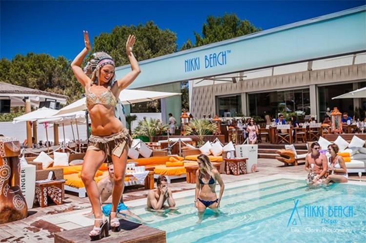 Nikki Beach beachclub Ibiza exotic dancer by the swimming pool people swimming drinking