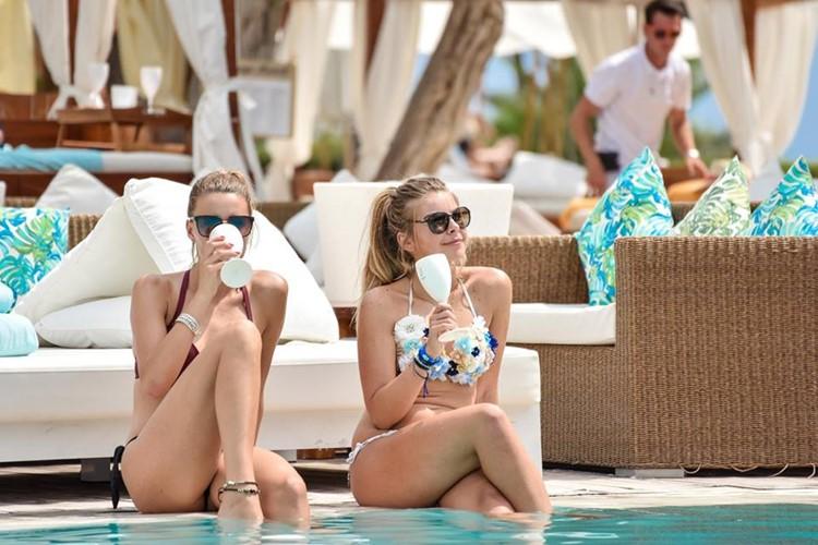 Nikki Beach beachclub Ibiza two pretty girls drinking by the swimming pool in bikinis