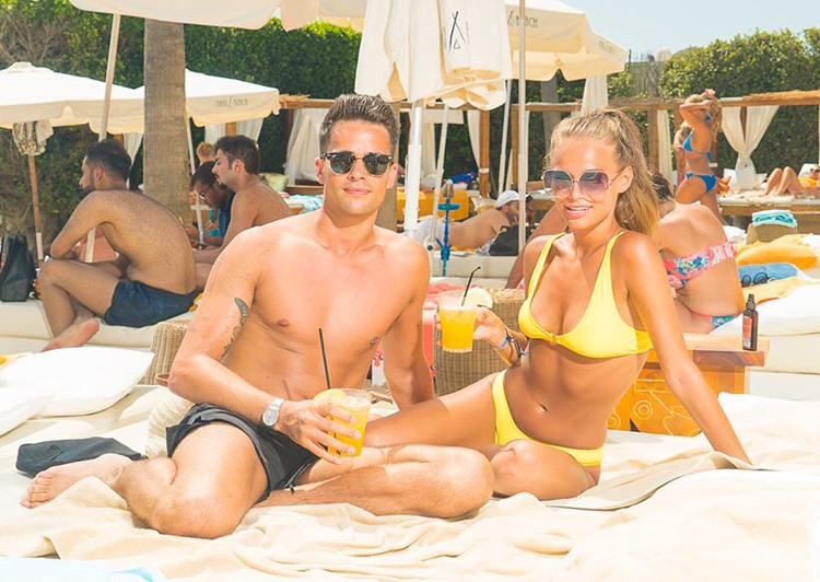 Nikki Beach beachclub Marbella pretty girl and boy laying sun tanning by the swimming pool