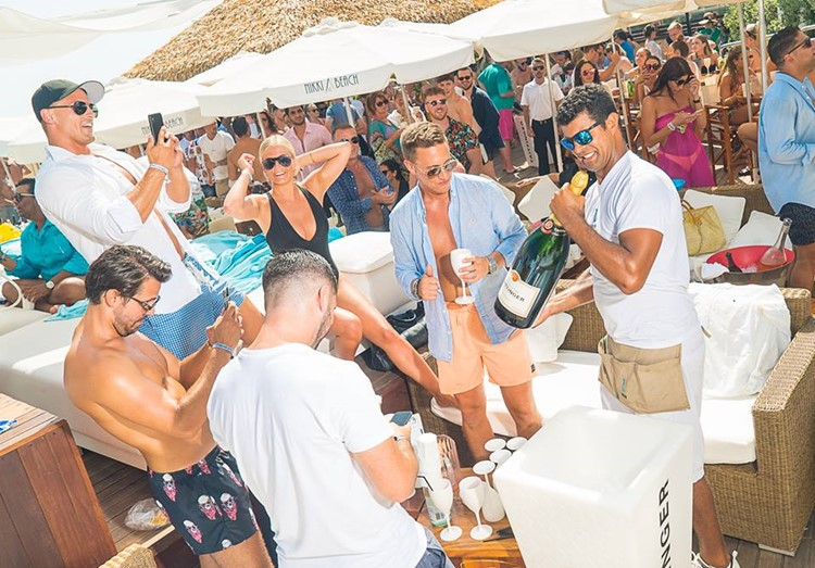 Nikki Beach beachclub Marbella men having fun drinking bottles of alcohol champagne
