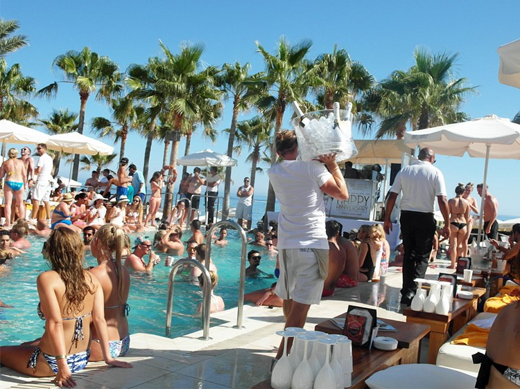 Nikki Beach beachclub Marbella people having fun by the swimming pool girls dancing