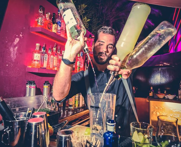 pacha nightclub ibiza barman pouring and mixing alcohol drinks at the bar