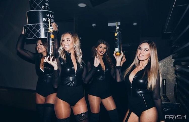 Prysm nightclub Chicago four blonde brunette girls dressed in black leather bodysuits holding bottles of champagne