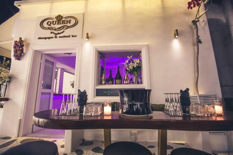 Queen of Mykonos nightclub view of the exterior of the club purple lights inside table full of glasses and alcohol