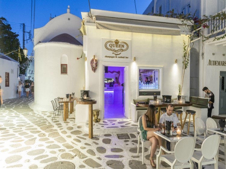Queen of Mykonos nightclub view of the club's exterior a couple sitting at a table having drinks
