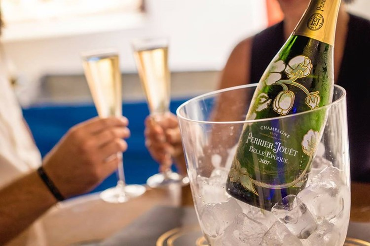 Queen of Mykonos nightclub bottle of champagne Perrier-Jouet being served at an event