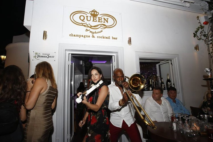 Queen of Mykonos nightclub musicians playing violin and trumpet at a concert outside