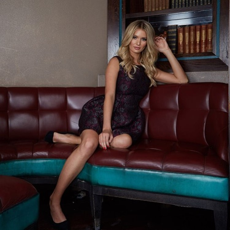 raffles nightclub london beautiful blonde woman dressed in elegant burgundy dress and black high heels having a photoshoot inside the club on couch