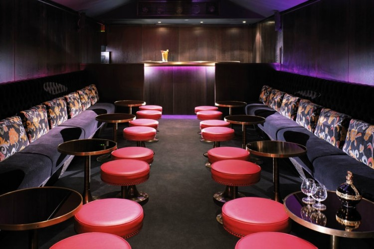 raffles nightclub london view of private tables and couches luxury interior design purple colored lights and furniture