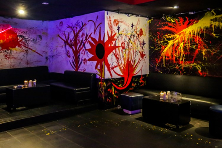 Stadium nightclub Toronto view of lounge area abstract painted walls orange yellow red black interior design