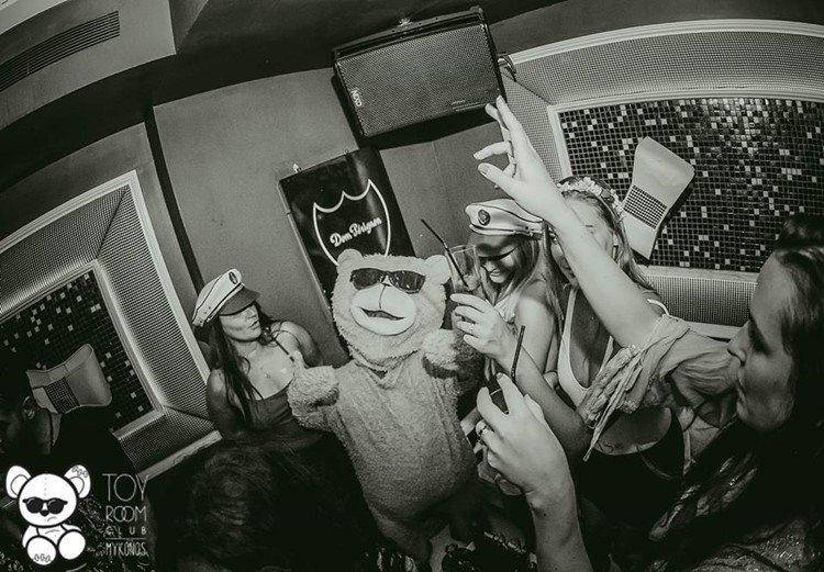 Toy RoOm nightclub Mykonos mascot teddy bear wearing sunglasses having fun with group of girls drinking alcohol