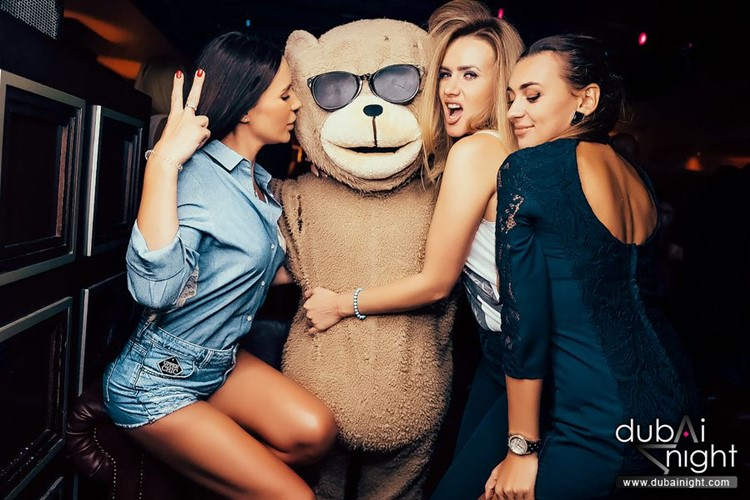 Toy Room nightclub Dubai brunette and blonde girls hugging and kissing mascot teddy bear