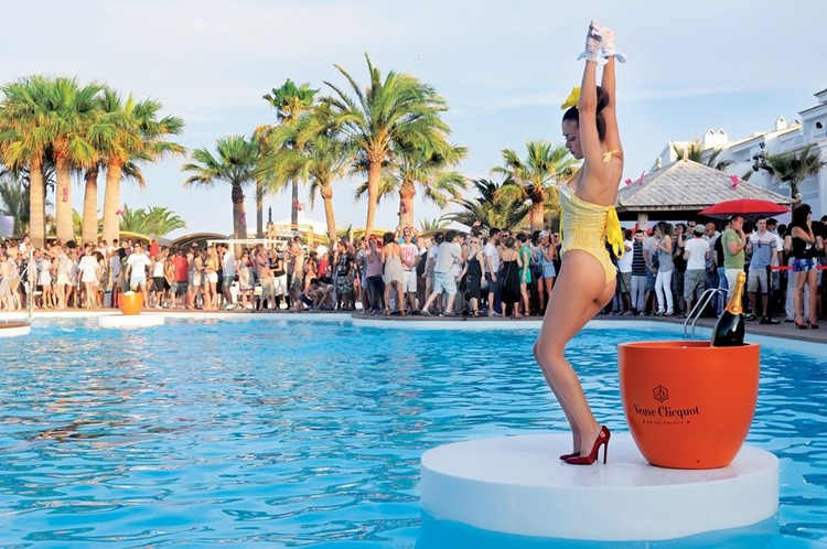 Ushuaia nightclub Ibiza sexy girl dancers dancing on the swimming pool in red high heels wearing yellow swimsuit