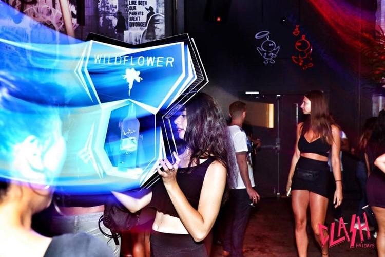 Wildflower nightclub Toronto girl holding alcohol bottles sign