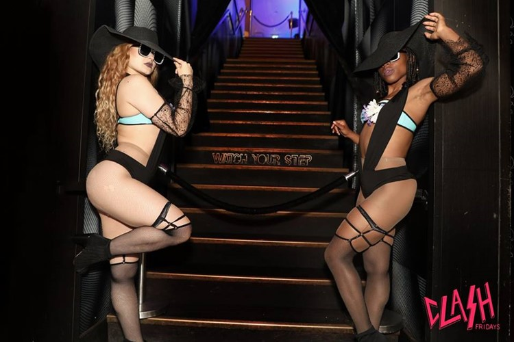 Wildflower nightclub Toronto two sexy exotic dancers dressed in black lingerie and hats next to stairs club entrance