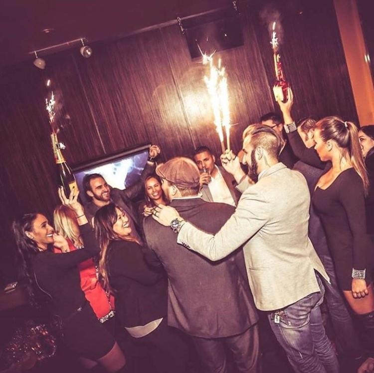 Ybar nightclub Chicago girls and men having fun holding champagne bottles